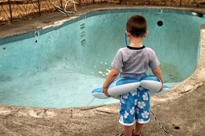 Pool Leak Detection - YardDoc - Austin, TX - Small boy standing next to empty pool with floatation device