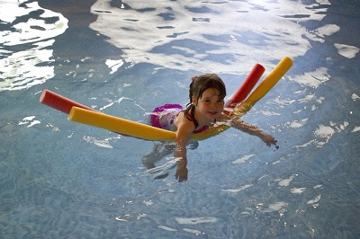 Pool Safety - YardDoc - Austin, TX - Little girl in pool with floatation noodles