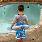 Swimming Pool Maintenance - Austin, TX - Boy with floatation device standing next to empty pool - YardDoc